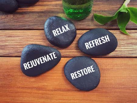 Motivierende und inspirierende Worte - Entspannen, erfrischen, verjüngen, wiederherstellen, geschrieben auf Kieselsteinen.