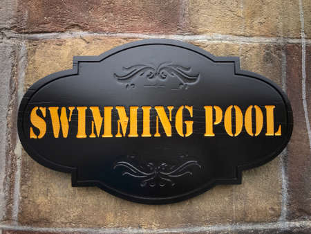 Signage of a swimming pool on the wall.