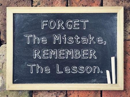 Motivierende und inspirierende Formulierung - Vergessen Sie den Fehler, erinnern Sie sich an die Lektion, die auf eine Tafel geschrieben wurde. Standard-Bild