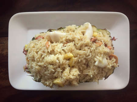 Food - Thai pineapple seafood fried rice served in a white plate.