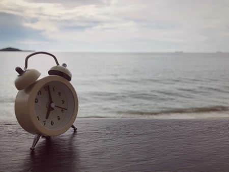 An alarm clock on a wooden table on background of a sea.