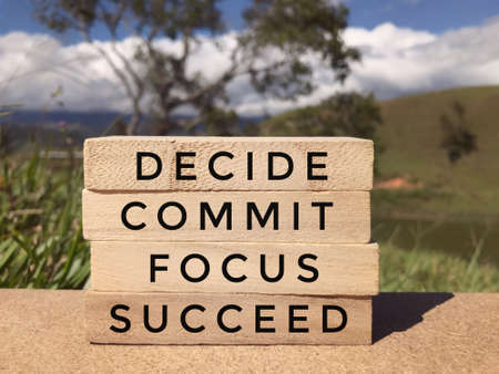 Motivational and inspirational wording - Decide, Commit, Focus, Succeed written on wooden blocks. Blurred styled background. Foto de archivo