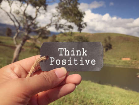 Motivational and inspirational wording - Think Positive written on a paper tag. Blurred styled background.