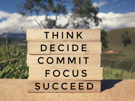 Motivational and inspirational wording - Think, Decide, Commit, Focus, Succeed written on wooden blocks. Blurred styled background.