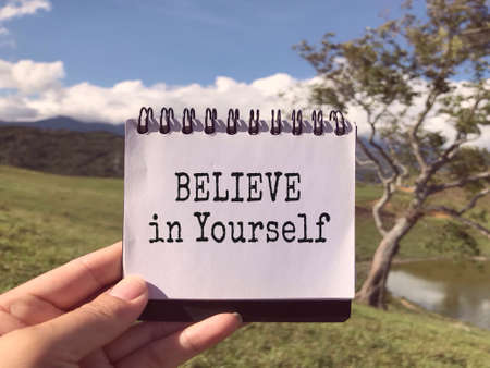 Motivational and inspirational wording - Believe In Yourself written on a notepad. Blurred styled background.