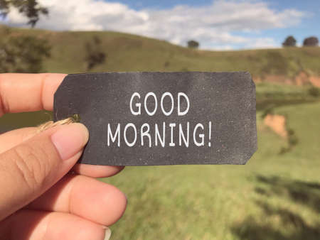 Greeting and inspirational wording - Good Morning written on a paper. Blurred styled background. Stock Photo