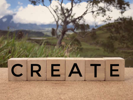 Motivational and inspirational word - CREATE written on wooden blocks. Blurred styled background.
