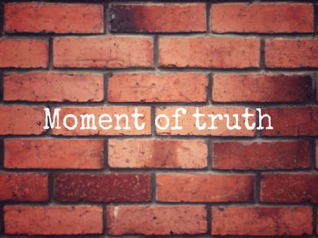 Motivational and inspirational wording - Moment Of Truth written on a brick wall. Blurred styled background. Stock Photo