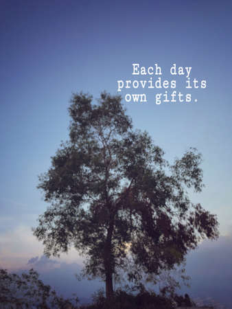 Motivational and inspirational wording - Each day provides its own gifts. Blurred styled background. Stock Photo