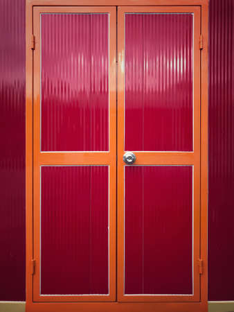 A closed red metal doors of a building located in Perak, Malaysia.