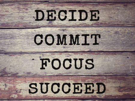 Motivational and inspirational wording - Decide, Commit, Focus, Succeed written on wooden planks. Blurred styled background.