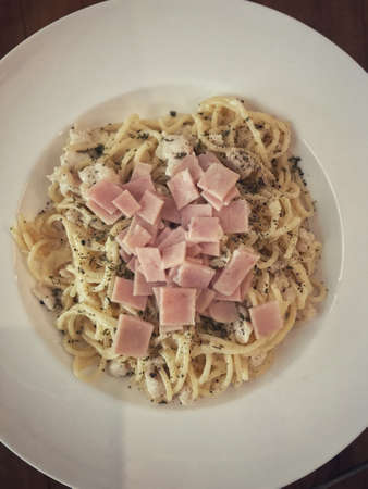 A plate of creamy spaghetti carbonara with ham topping.
