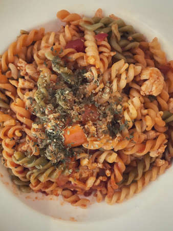 A plate of fusilli pasta with tomato sauce.