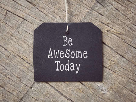 Motivational and inspirational wording - Be Awesome Today written on a paper. Blurred styled background. Stock Photo