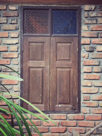 A weathered and closed wooden windows of a building.