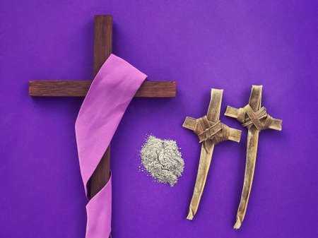 Good Friday, Palm Sunday, Ash Wednesday, Lent Season and Holy Week concept.  A Christian cross, ashes and crosses made of palm leaves on purple background.