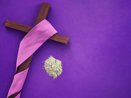 Good Friday, Palm Sunday, Ash Wednesday, Lent Season and Holy Week concept.  A Christian cross and ashes on purple background.