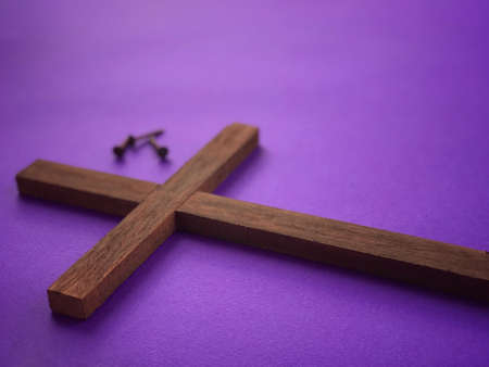 Good Friday, Palm Sunday, Ash Wednesday, Lent Season and Holy Week concept. A Christian cross and three rusty nails on purple background.