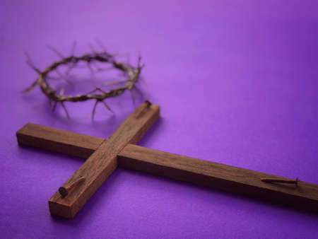 Good Friday, Palm Sunday, Ash Wednesday, Lent Season and Holy Week concept.  A Christian cross, three rusty nails and a woven crown of thorns on purple background.