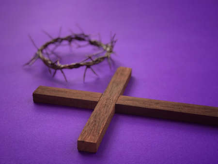 Good Friday, Palm Sunday, Ash Wednesday, Lent Season and Holy Week concept. A Christian cross and a woven crown of thorns on purple background.