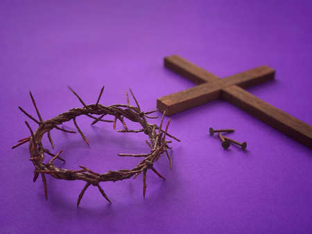 Good Friday, Palm Sunday, Ash Wednesday, Lent Season and Holy Week concept. A woven crown of thorns, three rusty nails and a Christian cross on purple background. Archivio Fotografico
