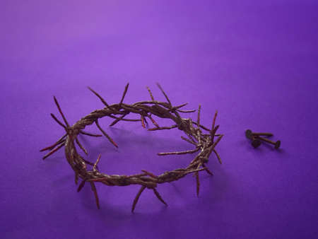 Good Friday, Lent Season and Holy Week concept - A woven crown of thorns an three nails on purple background.