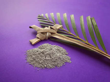Good Friday, Palm Sunday, Ash Wednesday, Lent Season and Holy Week concept. A Christian cross, ashes and a palm leaf on purple background. Archivio Fotografico