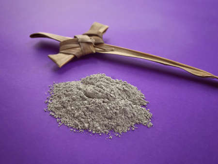 Good Friday, Palm Sunday, Ash Wednesday, Lent Season and Holy Week concept.  A Christian cross made of palm leaf and ashes on purple background.