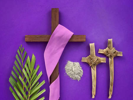 Good Friday, Palm Sunday, Ash Wednesday, Lent Season and Holy Week concept. A Christian cross, ashes, crosses made of palm leaves and palm leaves on purple background. Archivio Fotografico
