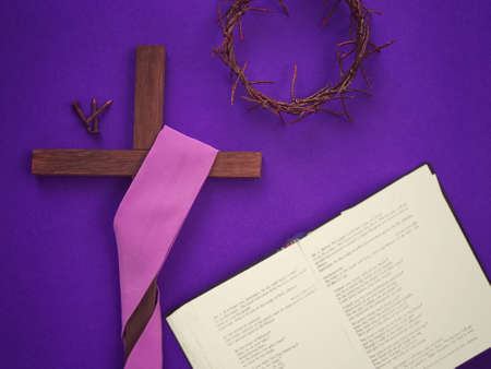 Good Friday, Lent Season, Ash Wednesday and Holy Week concept. A Christian cross, three rusty nails, a woven crown of thorns and a bible on purple background. Archivio Fotografico
