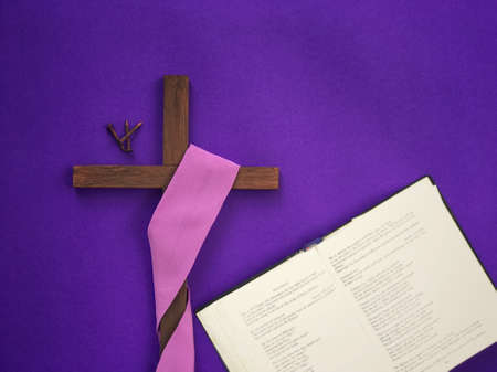 Good Friday, Lent Season, Ash Wednesday and Holy Week concept. A Christian cross, three rusty nails and a bible on purple background.