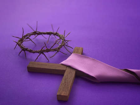 Good Friday, Lent Season, Ash Wednesday and Holy Week concept. A woven crown of thorns and a Christian cross on purple background.