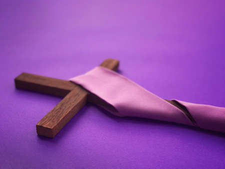 Good Friday, Lent Season, Ash Wednesday and Holy Week concept. A Christian cross on purple background.