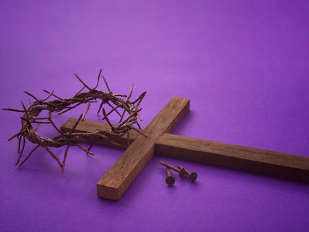 Good Friday, Lent Season, Ash Wednesday and Holy Week concept. A woven crown of thorns, three rusty nails and a Christian cross on purple background.