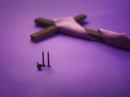 Good Friday, Lent Season, Ash Wednesday and Holy Week concept. A Christian cross and three rusty nails on purple background. Archivio Fotografico