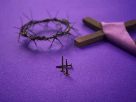 Good Friday, Lent Season, Ash Wednesday and Holy Week concept. A woven crown of thorns, three rusty nails and Christian cross on purple background.