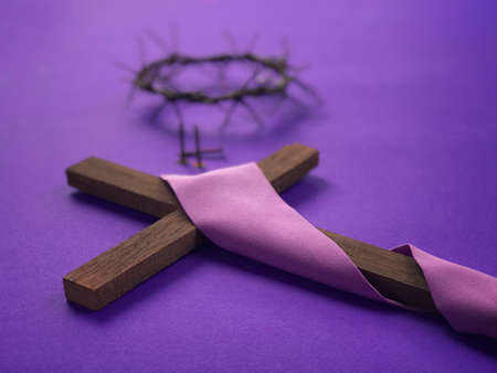 Good Friday, Lent Season, Ash Wednesday and Holy Week concept. Christian cross, a woven crown of thorns and three rusty nails  on purple background. Archivio Fotografico