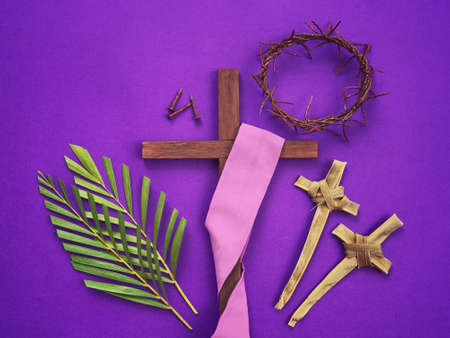 Good Friday, Lent Season, Palm Sunday, Ash Wednesday and Holy Week concept. A Christian cross, three rusty nails, woven crown of thorns, crosses made of palm leaves and palm leaves on purple background.