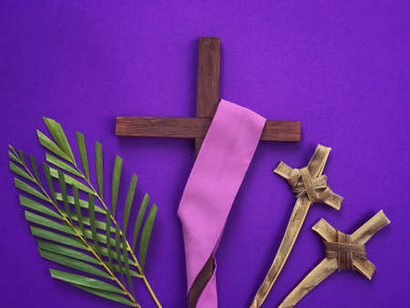 Good Friday, Palm Sunday, Lent Season, Ash Wednesday and Holy Week concept.  A Christian cross, crosses made of palm leaves and palm leaves on purple background.