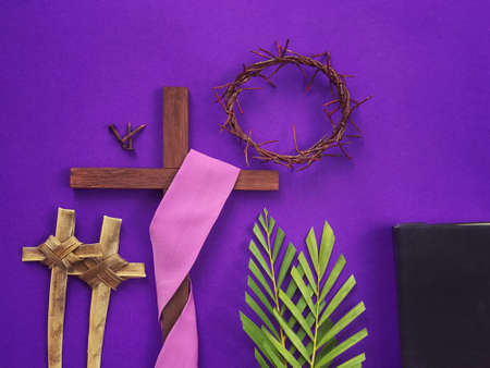 Good Friday, Lent Season, Palm Sunday, Ash Wednesday and Holy Week concept.  A Christian cross, three rusty nails, woven crown of thorns, crosses made of palm leaves, palm leaves and a bible on purple background. Archivio Fotografico