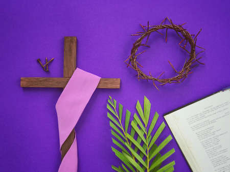 Good Friday, Palm Sunday, Lent Season and Holy Week concept. A Christian cross, three rusty nails, woven crown of thorns, palm leaves and a bible on purple background.
