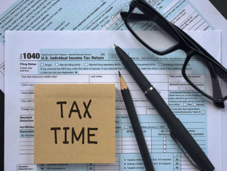 Tax-filling concept - 'Tax time' written on a paper, a pencil, a pen, eyeglasses, featuring half of U.S IRS 1040 form.
