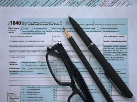 Tax-filling concept. A pencil, a pen, eyeglasses, featuring half of U.S IRS 1040 form. 版權商用圖片