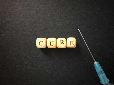 Health care and medical concept. CURE written on wooden blocks. Blurred styled background. Archivio Fotografico