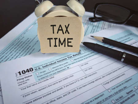 Tax-filling concept - TAX TIME written on a paper, pencil, a pen, a clock eyeglasses and featuring half of U.S IRS 1040 form. With vintage-styled background. 版權商用圖片