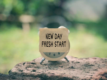 Motivational and inspirational wording. New Day Fresh Start written on a paper. Vintage styled background.