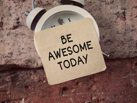 Motivational and inspirational wording. Be Awesome Today written on a paper that sticked on a clock. Vintage styled background.
