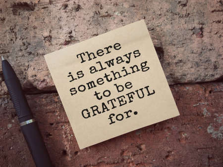 Motivational and inspirational wording. There Is Always Something To Be Grateful For written on an adhesive note. Vintage styled background. 版權商用圖片