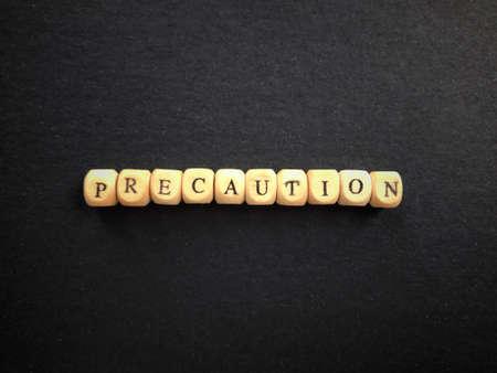 PRECAUTION written on wooden blocks.