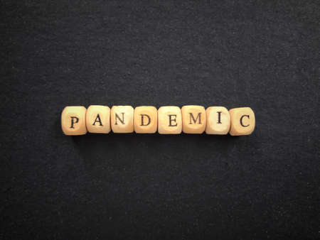 Global health and safety issue. PANDEMIC written on wooden blocks. Vintage styled background. 版權商用圖片
